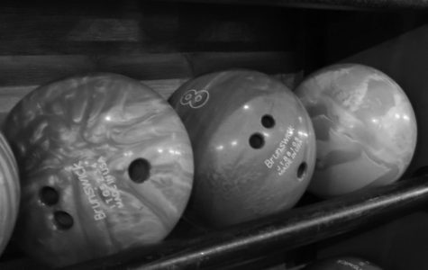 Bowling balls sit restlessly on the shelf awaiting their turn to roll down the lane.