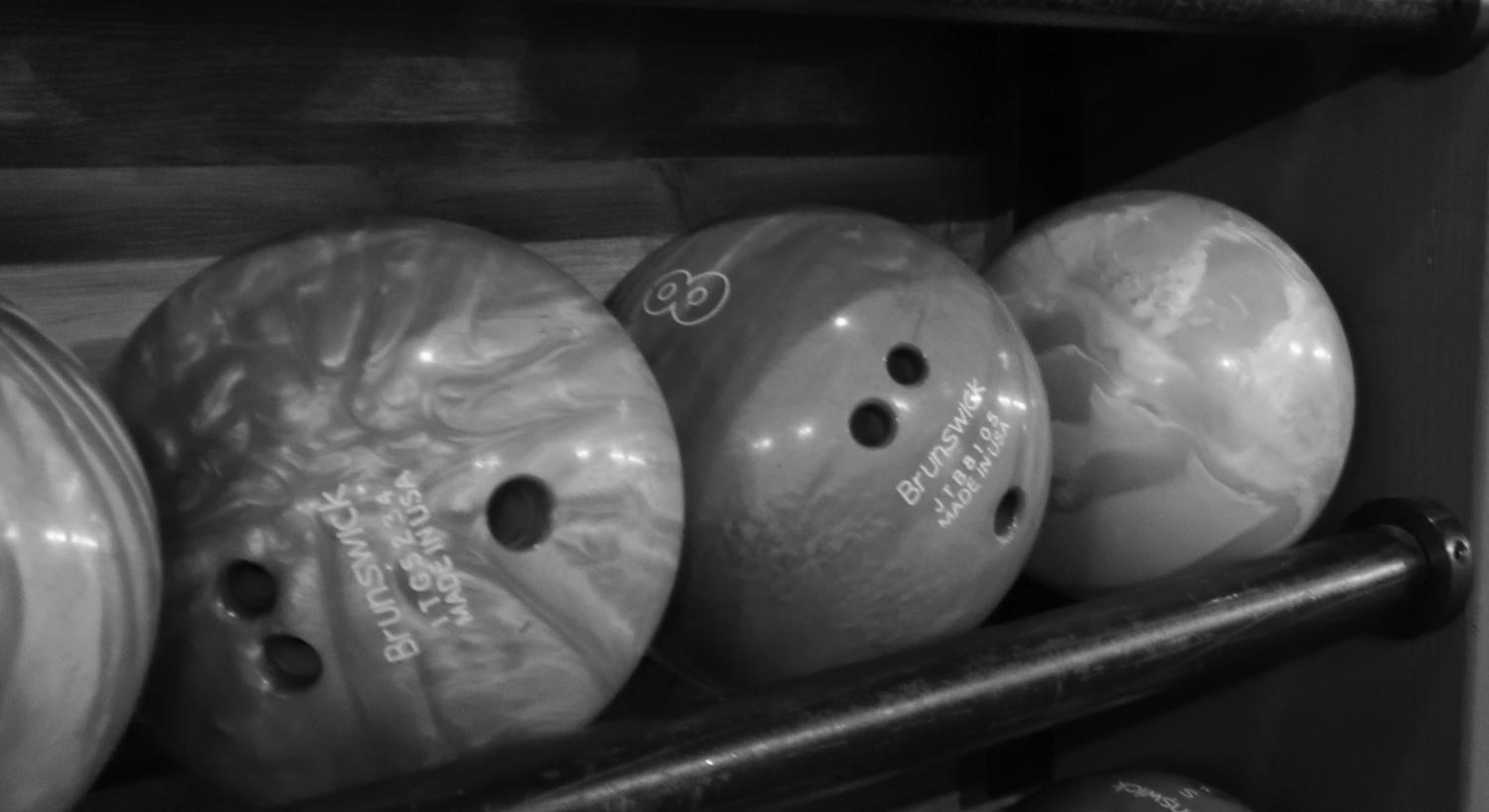 Bowling+balls+sit+restlessly+on+the+shelf+awaiting+their+turn+to+roll+down+the+lane.