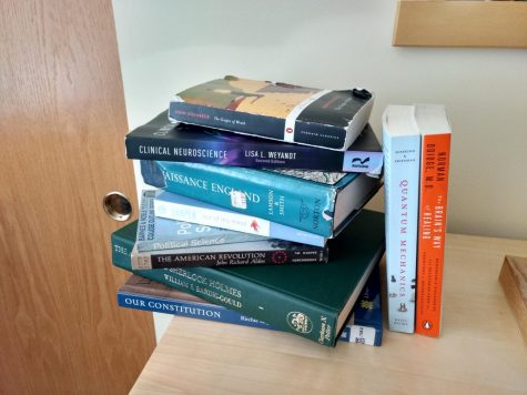 A wide assortment of books sit haphazardly on a dresser, awaiting to be read.